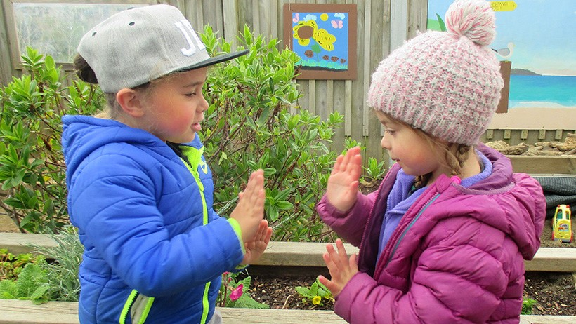 children playing hand clapping game at preschool